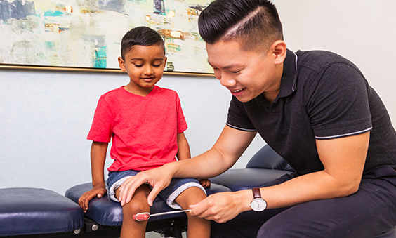 Chiropractor assessing boy's knee