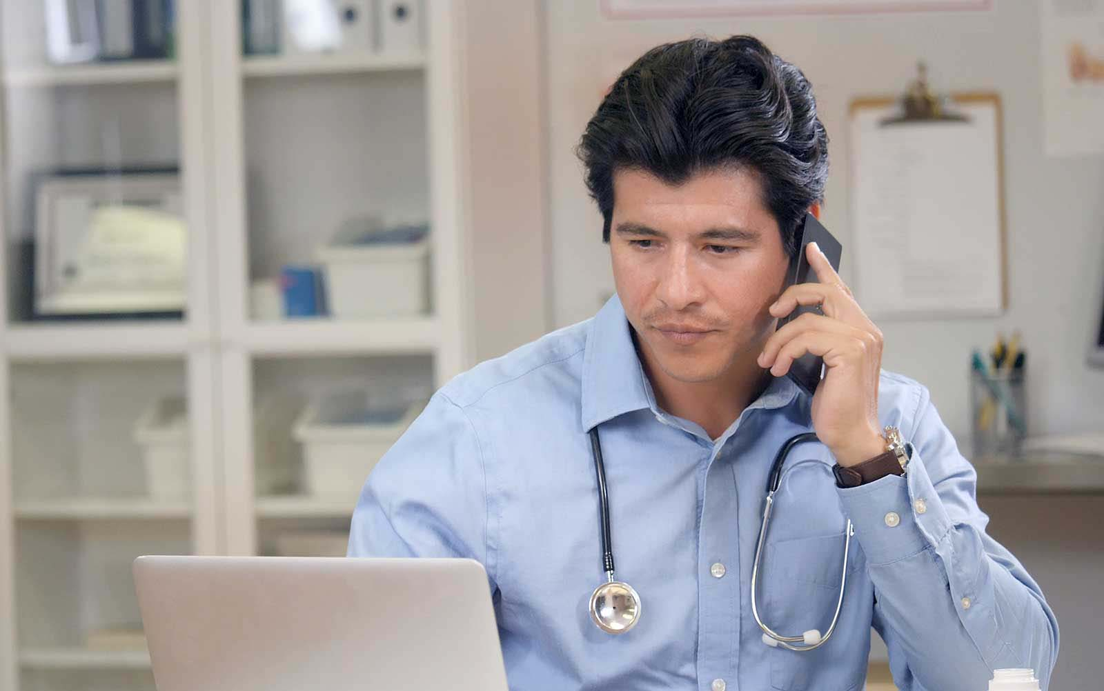 Male doctor on phone potentially with chiropractor and looking at computer