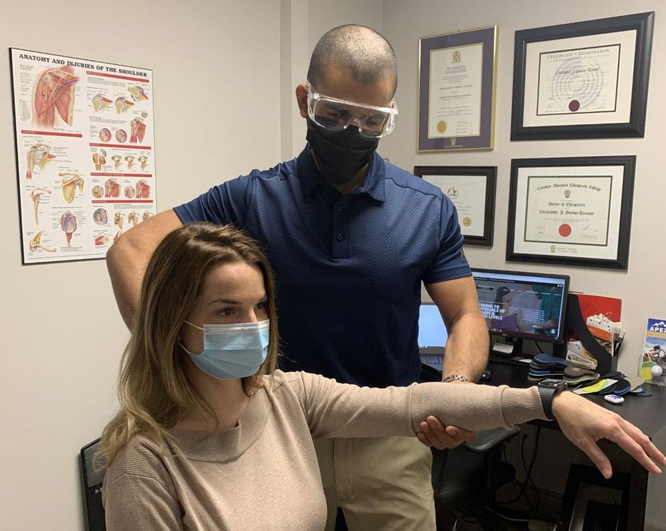 Dr. Gordon-Tennant assessing female patient's arm