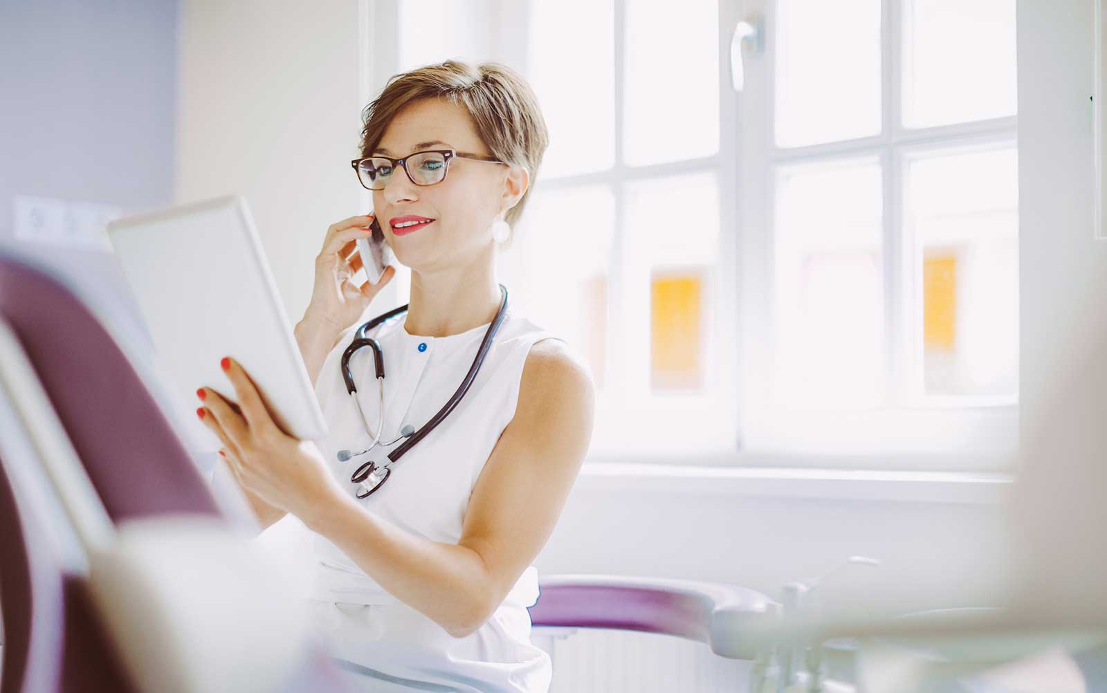 Female doctor on phone potentially with chiropractor and looking at tablet