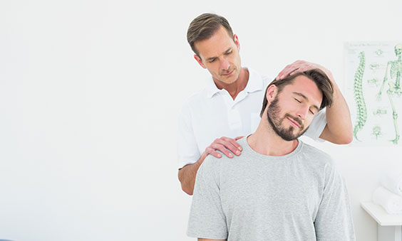Male chiropractor checking patient's neck to deliver chiropractic care