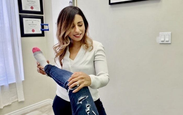 Female Chiropractor holding patients leg