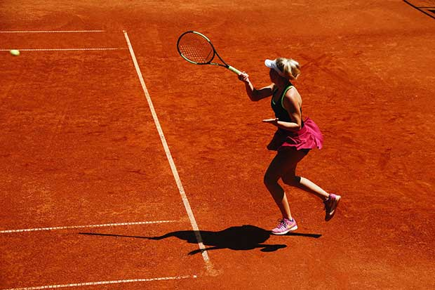 Woman playing tennis after recovering from a shoulder and arminjury